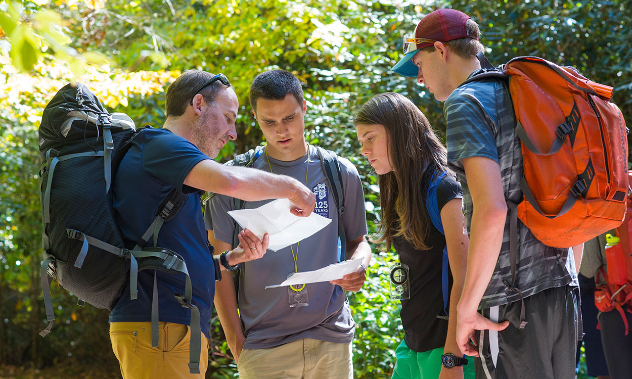 Andrew Bobilya teaches navigation skills on a hike with students