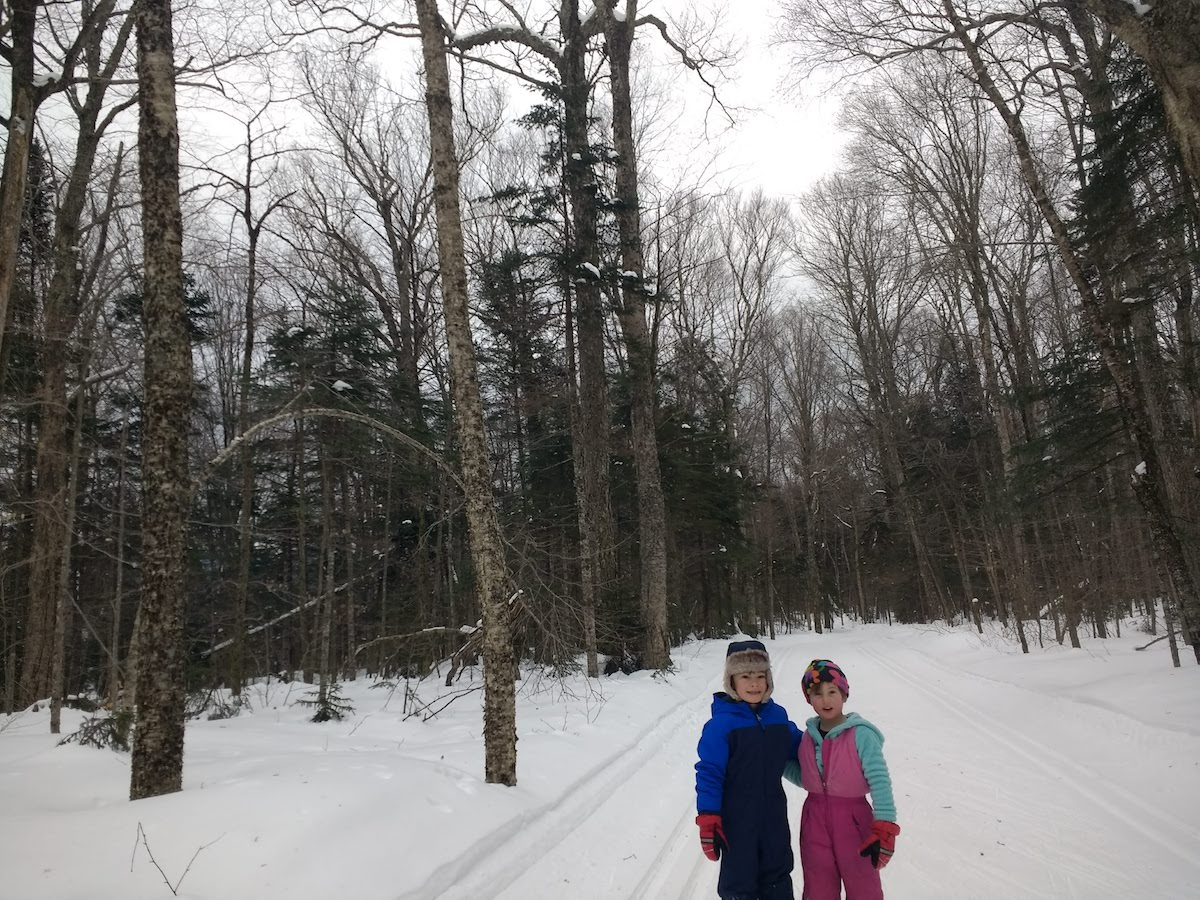 Two children smile for a photo while cross country skiing