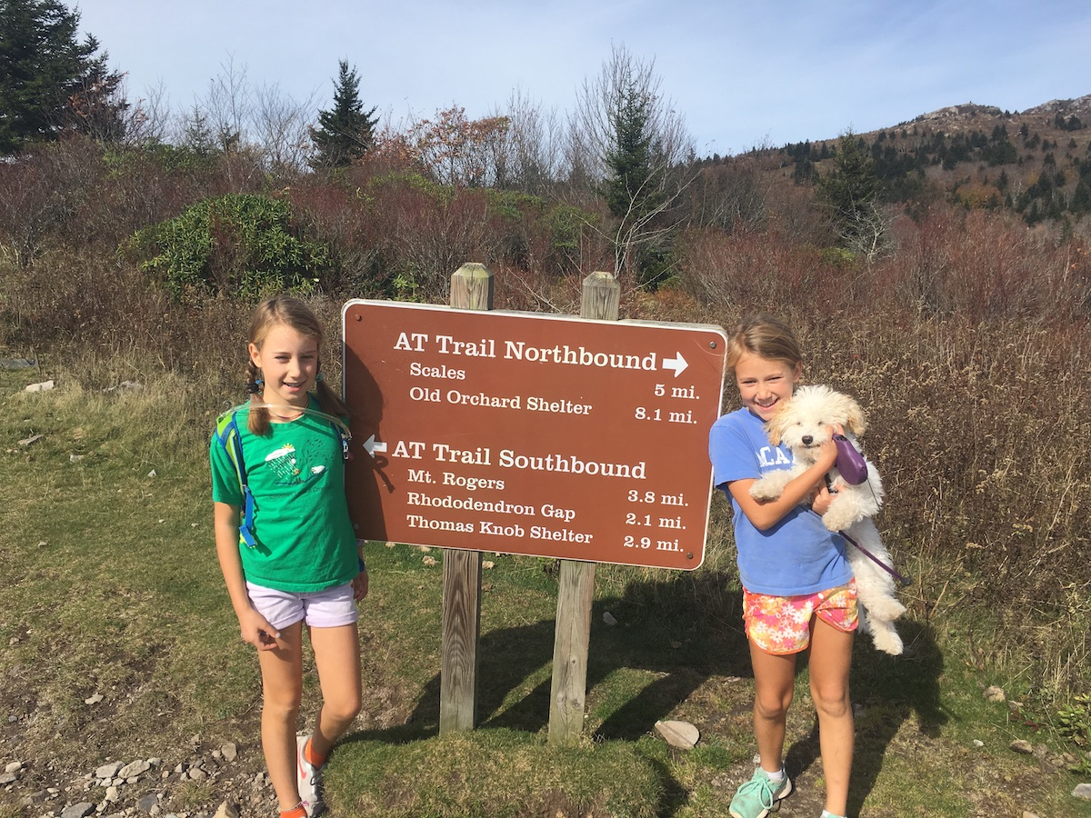 Andrew Bobilya's daughters smile next to a trailhead on a hike with their dog
