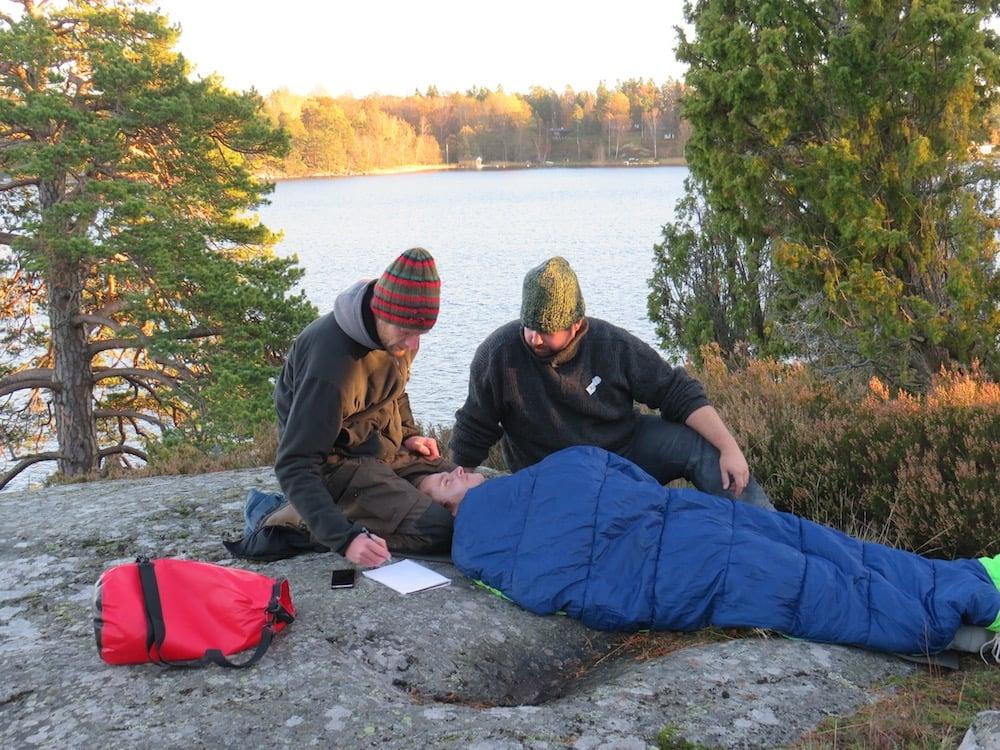 NOLS students care for a patient in a sleeping bag in a wilderness medicine scenario