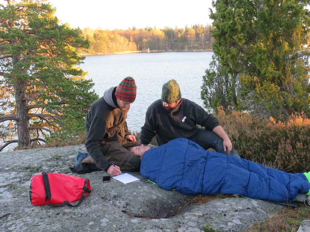 NOLS students care for a patient in a sleeping bag in a wilderness medicine scenario