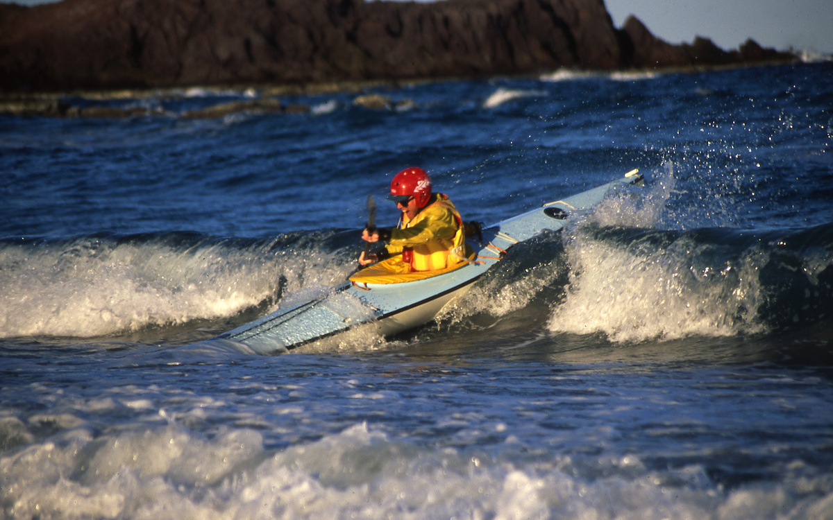 Smiling NOLS student paddles a sea kayak in the waves in Baja