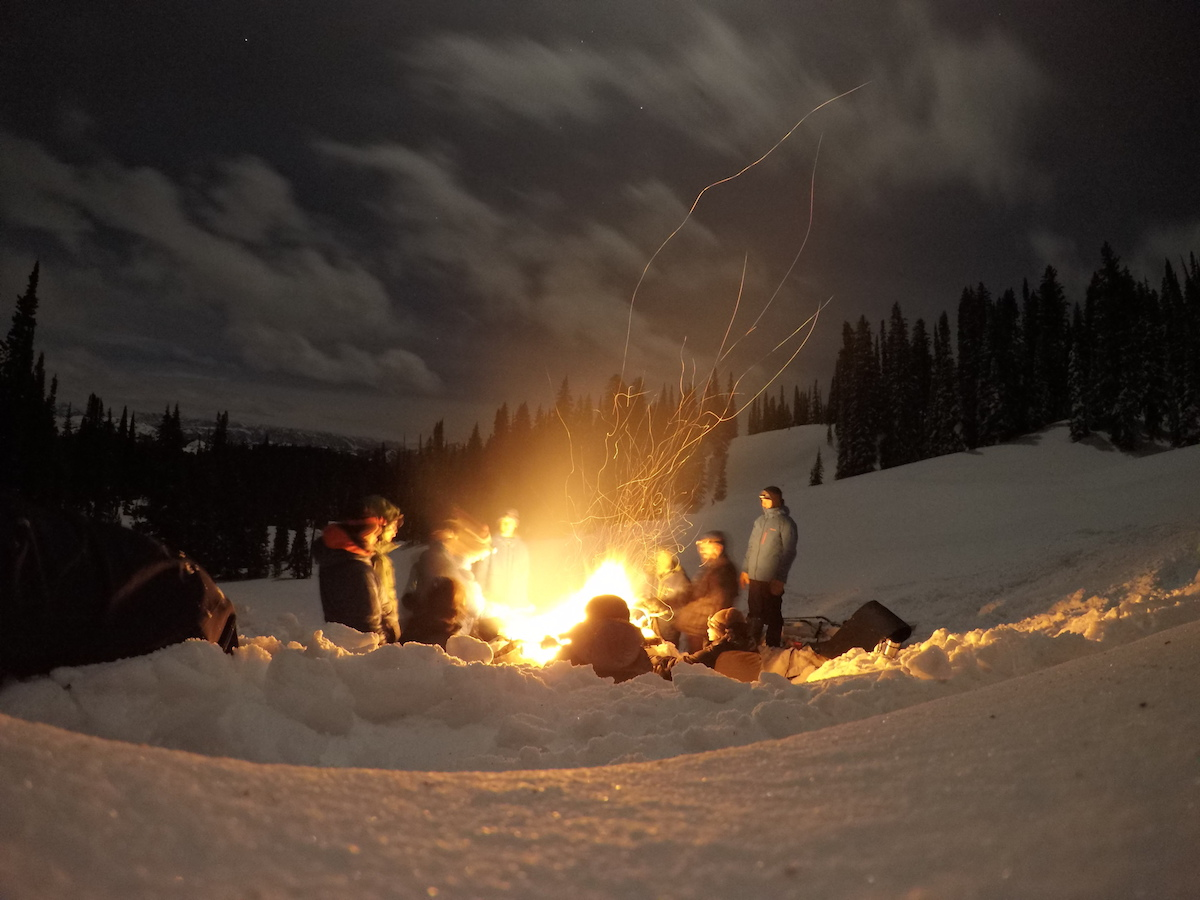 Group around a campfire at a winter campsite