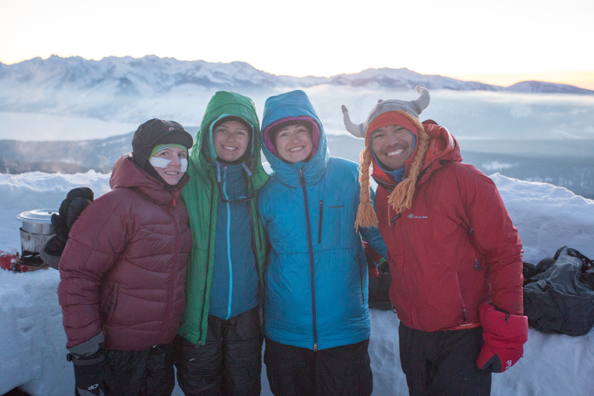 Four happy people smile in winter clothing with one wearing a fun hat