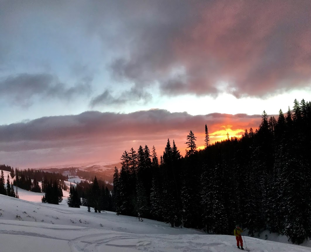 NOLS student backcountry skiing with sunrise in the backdrop