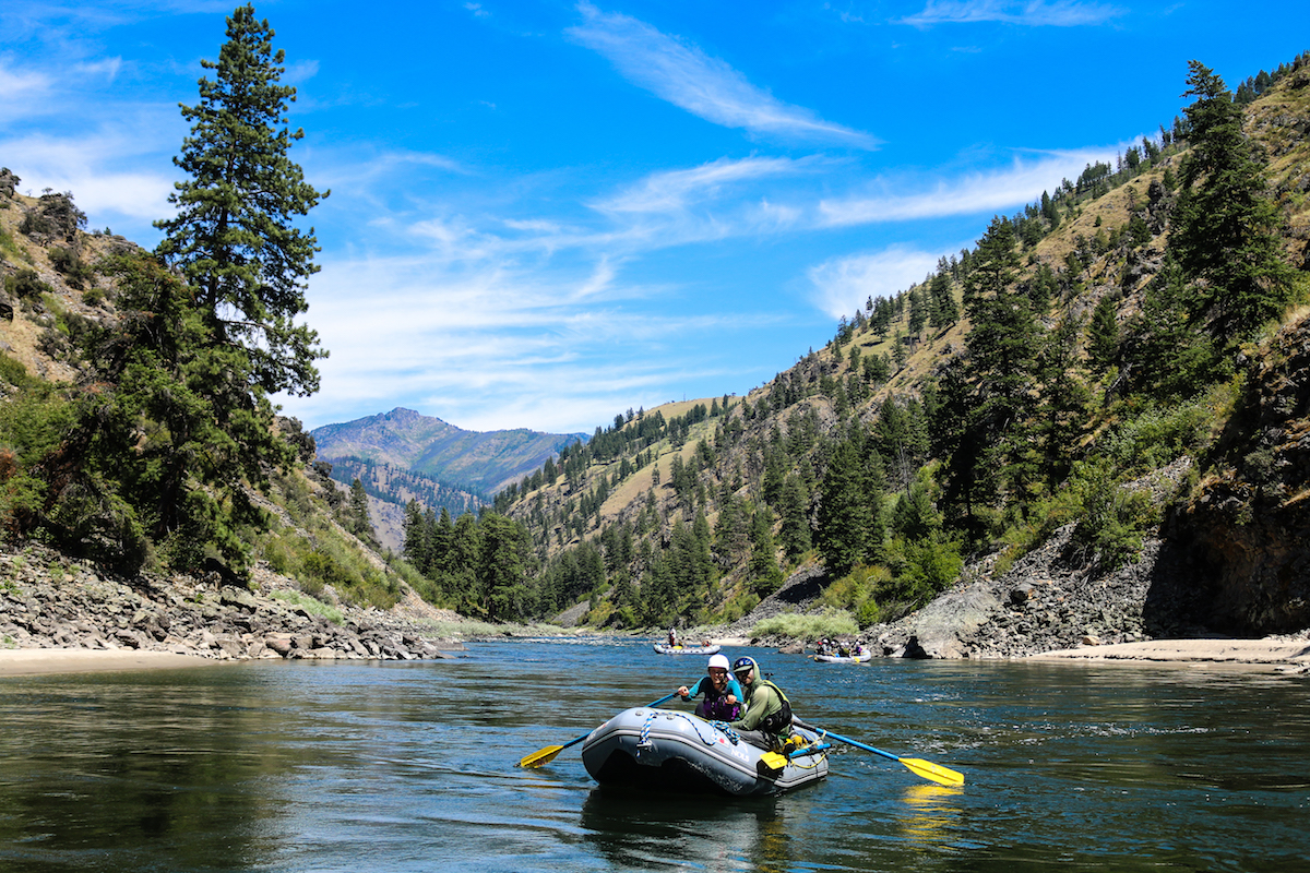 two NOLS participants paddle a raft on the Salmon River on a sunny day