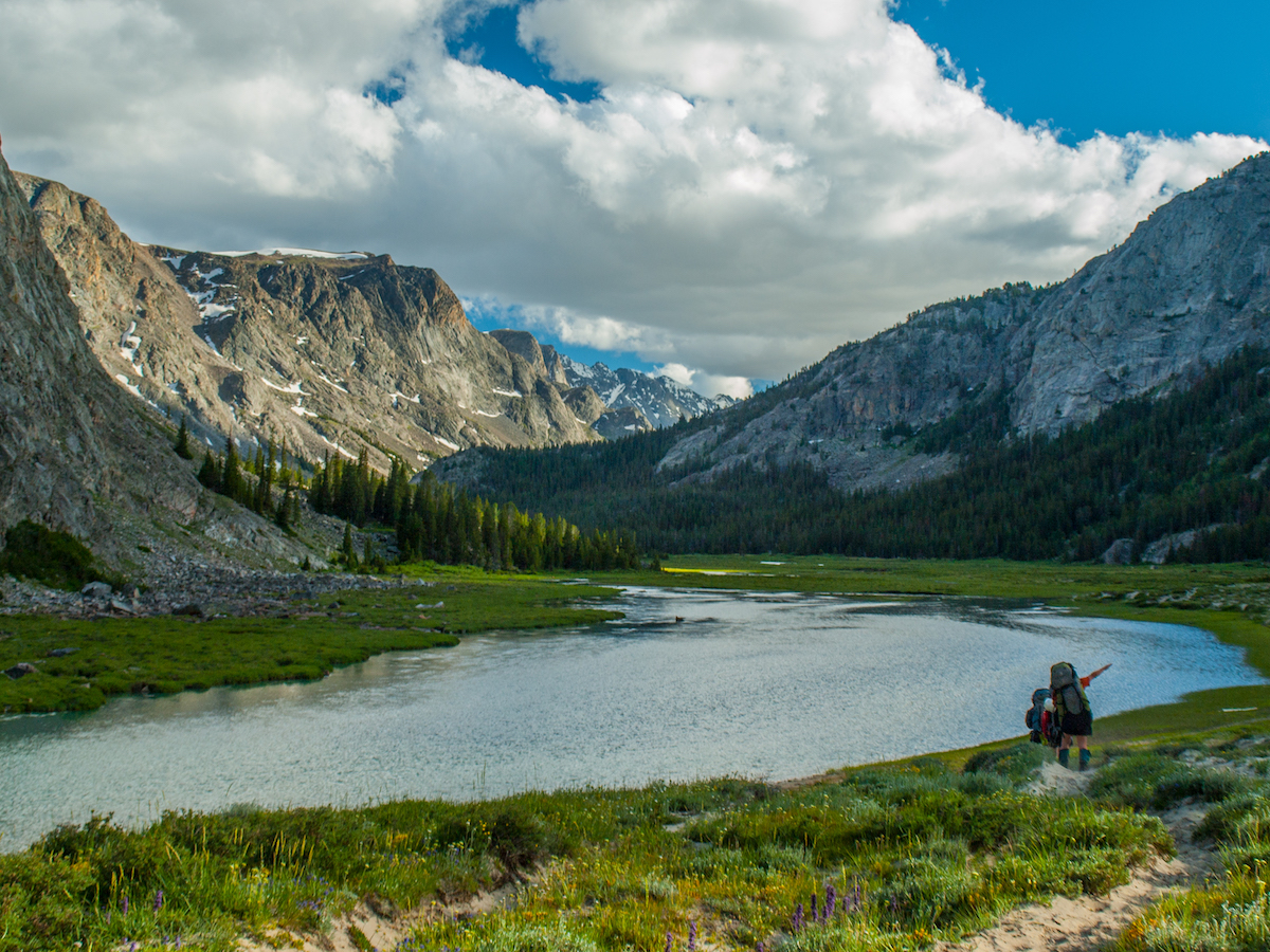 NOLS participants hike beside an alpine lake surrounded by rocky peaks in the Wind River Range