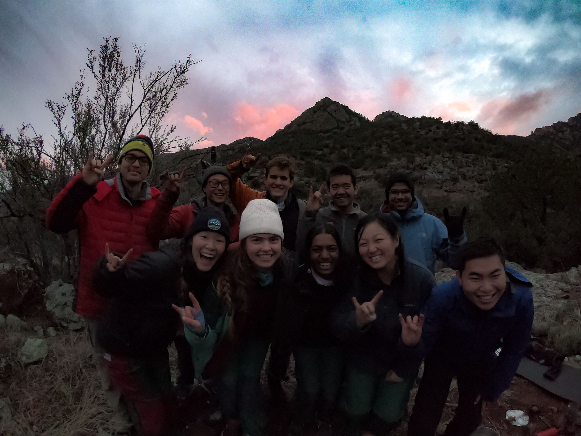 "A group of business school students on a NOLS expedition hold up ""rock on"" hand signals while the sun sets behind them."