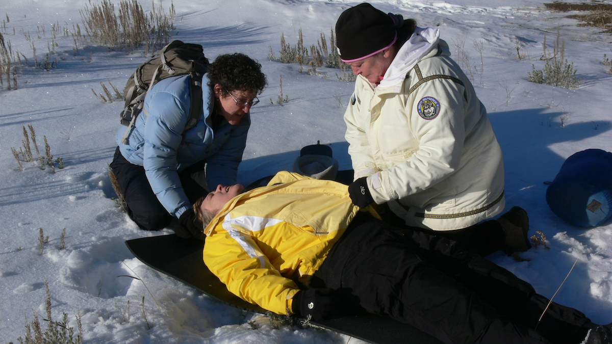 two NOLS Wilderness Medicine students kneel beside a patient in the snow and perform a mock initial assessment