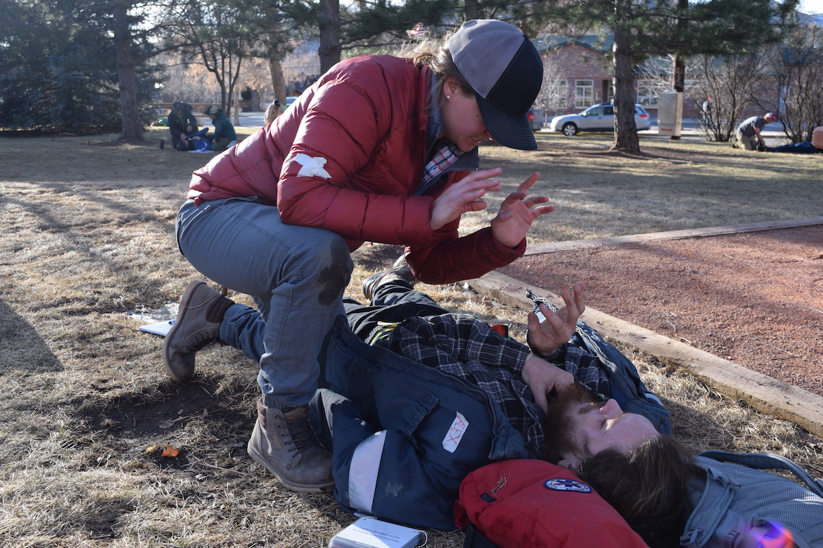 NOLS wilderness medicine students communicate in ASL while practicing patient care outdoors