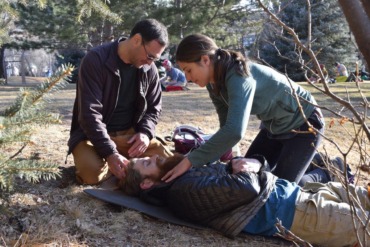 two NOLS Wilderness Medicine students practice caring for a patient with possible spine-injury mechanism
