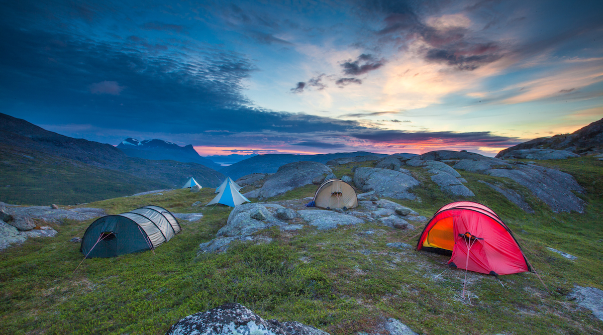 sunset over NOLS tents scattered between rocks in the mountains of Scandinavia