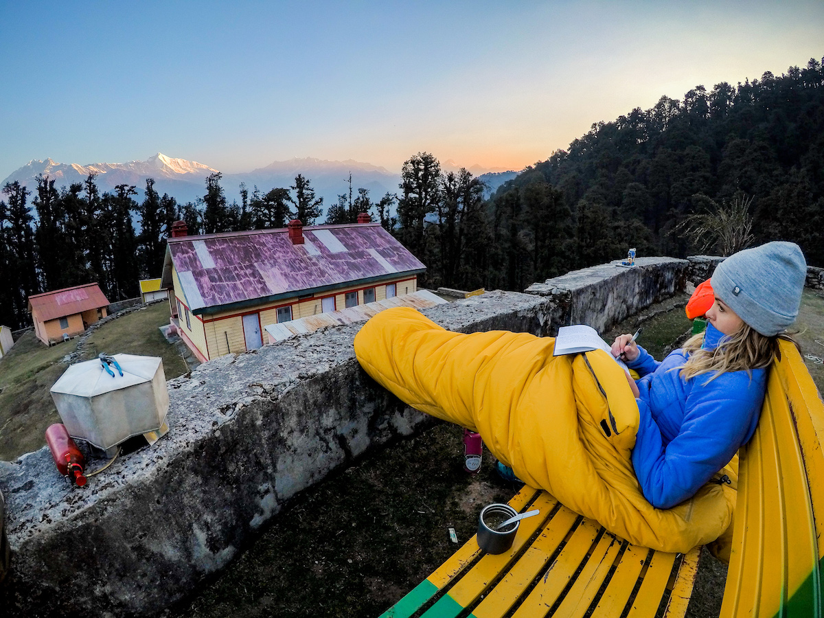 NOLS student wrapped in a sleeping bag sits on a bench journaling in the Himalaya