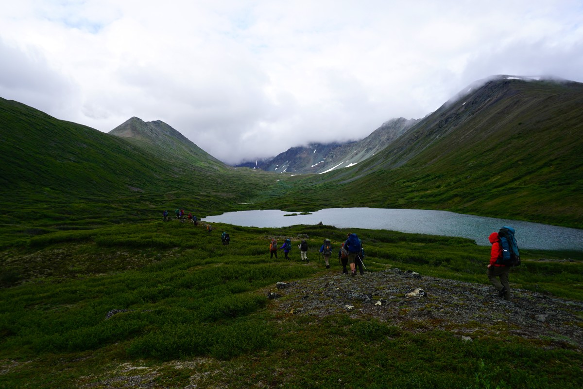 Backpackers hike along a lake in a lush mountain valley