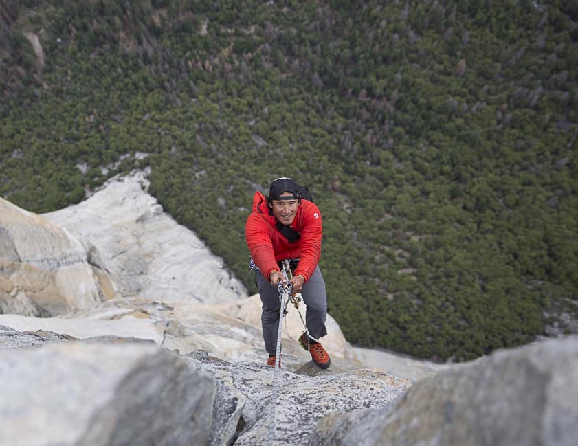 smiling Jimmy Chin rock climbing, as seen from above