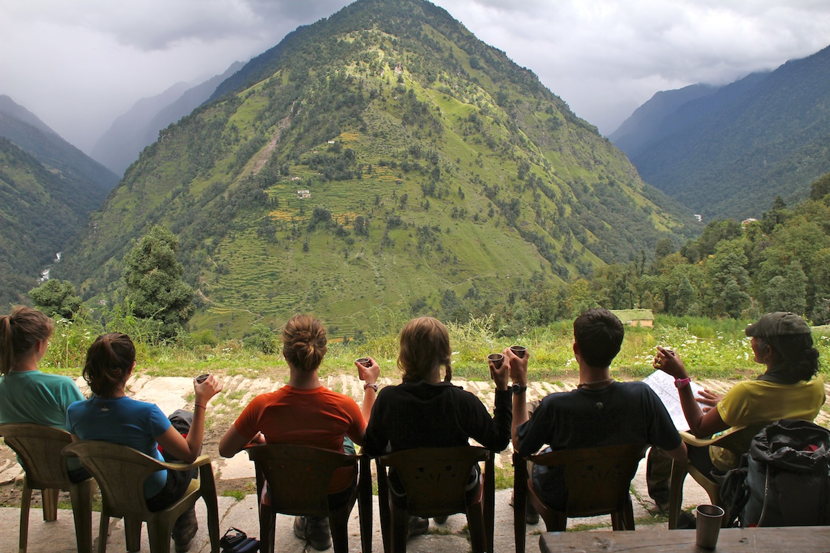 six NOLS students sit and enjoy chai and a view of the mountains while hiking in the Himalaya
