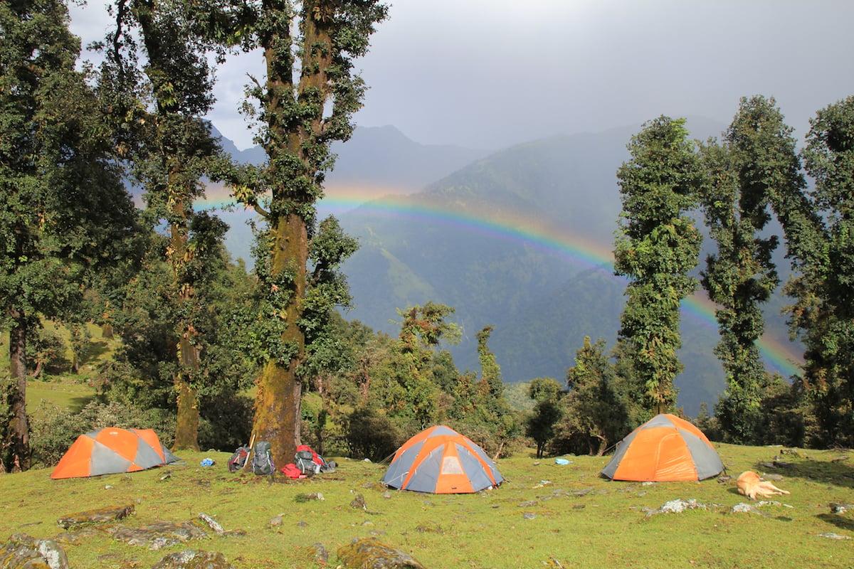 three NOLS tents in the Himalaya with a rainbow overhead
