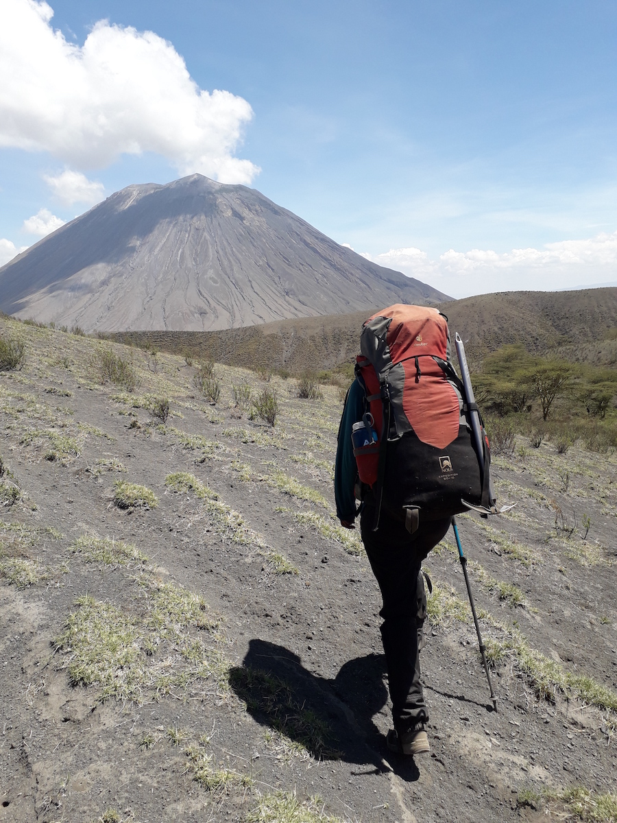 NOLS participant with backpack treks toward mountain