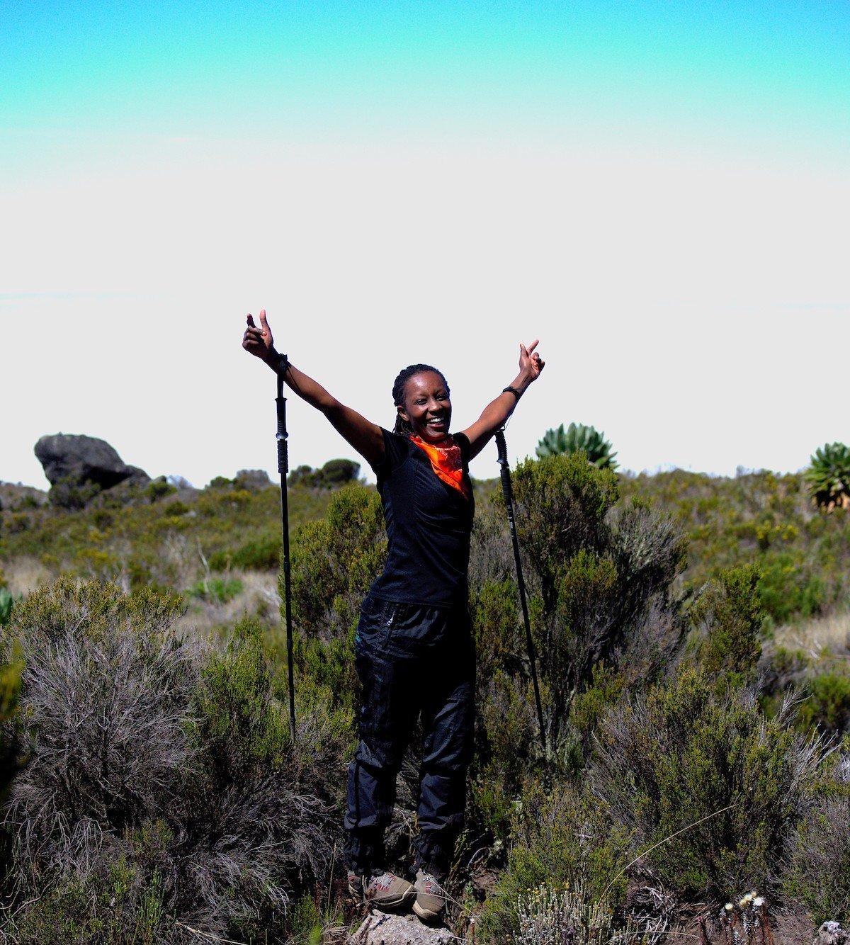 Carol Wanjiru smiles with trekking poles on the trail