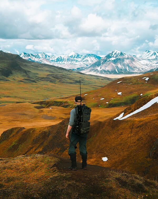 Person wearing large heavy backpack with mountain background