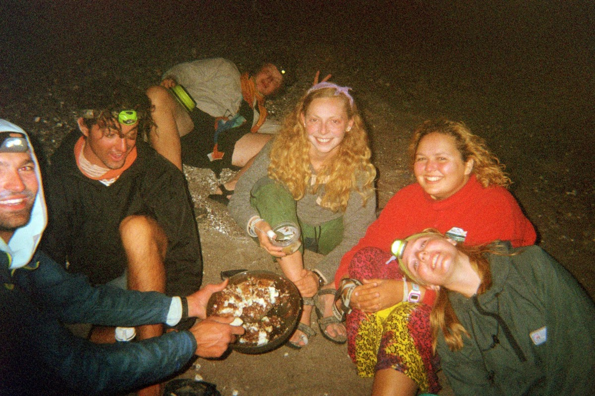 Six smiling NOLS students sit on the ground and show off their dinner