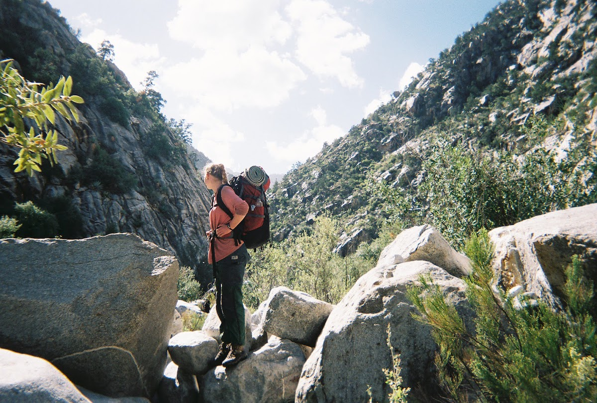 NOLS  student stands on boulders while hiking in Baja California