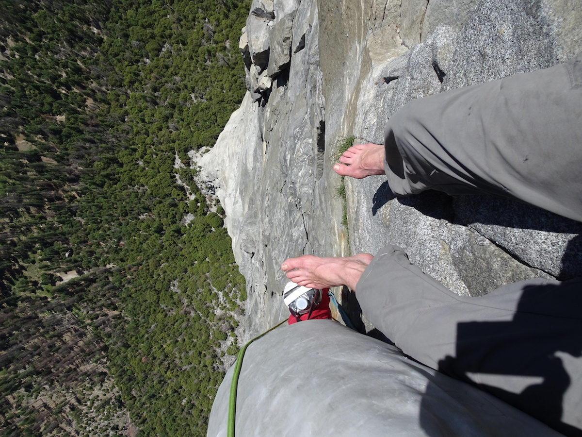 looking down on feet over a tall cliff