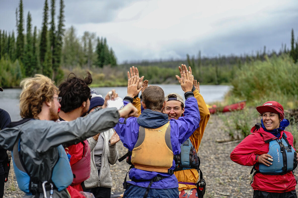 Students high five on the bank of a river.