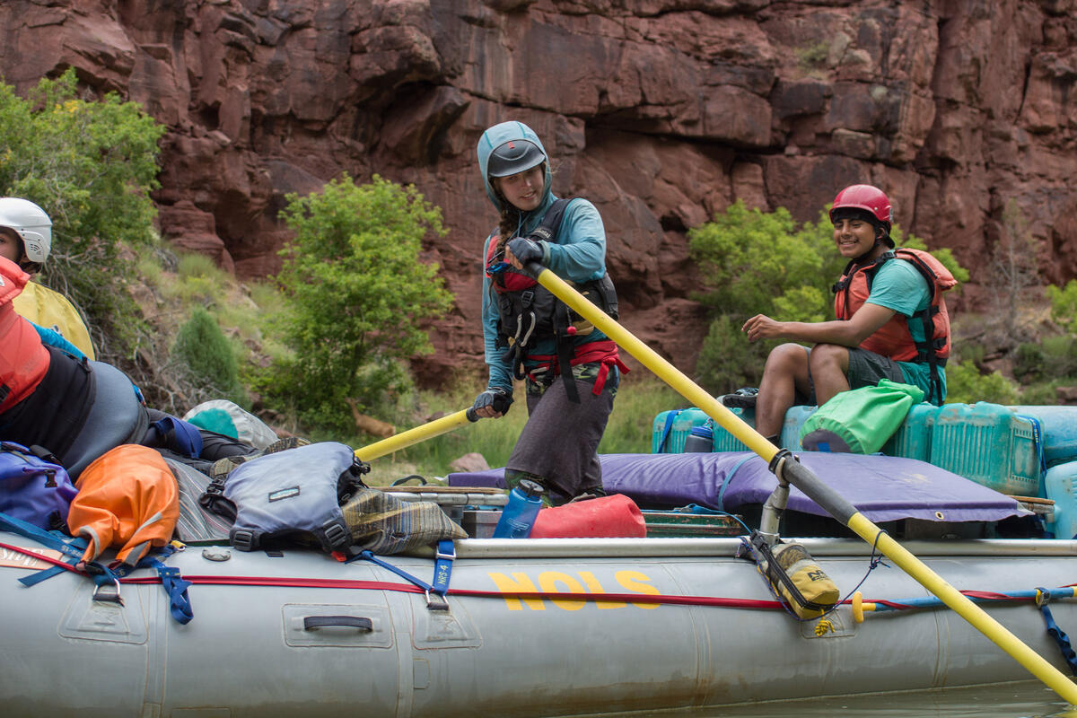 Students steer a boat on a river.