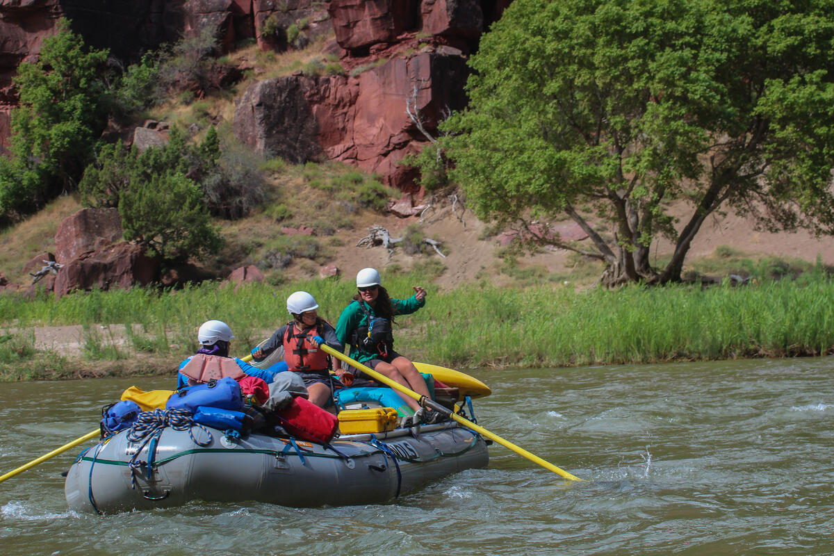 Students steer a raft down the river on a NOLS course.