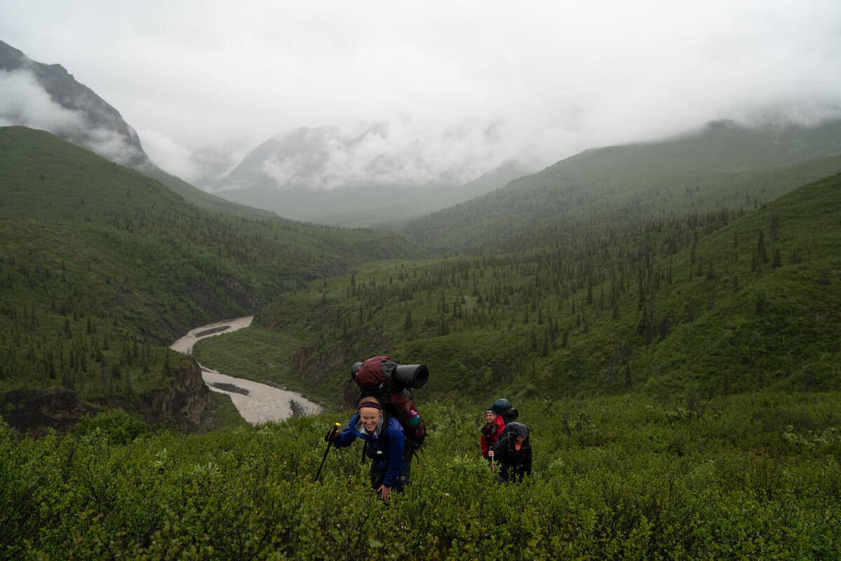 Students hike up a ravine in the rain on an Alaska course.