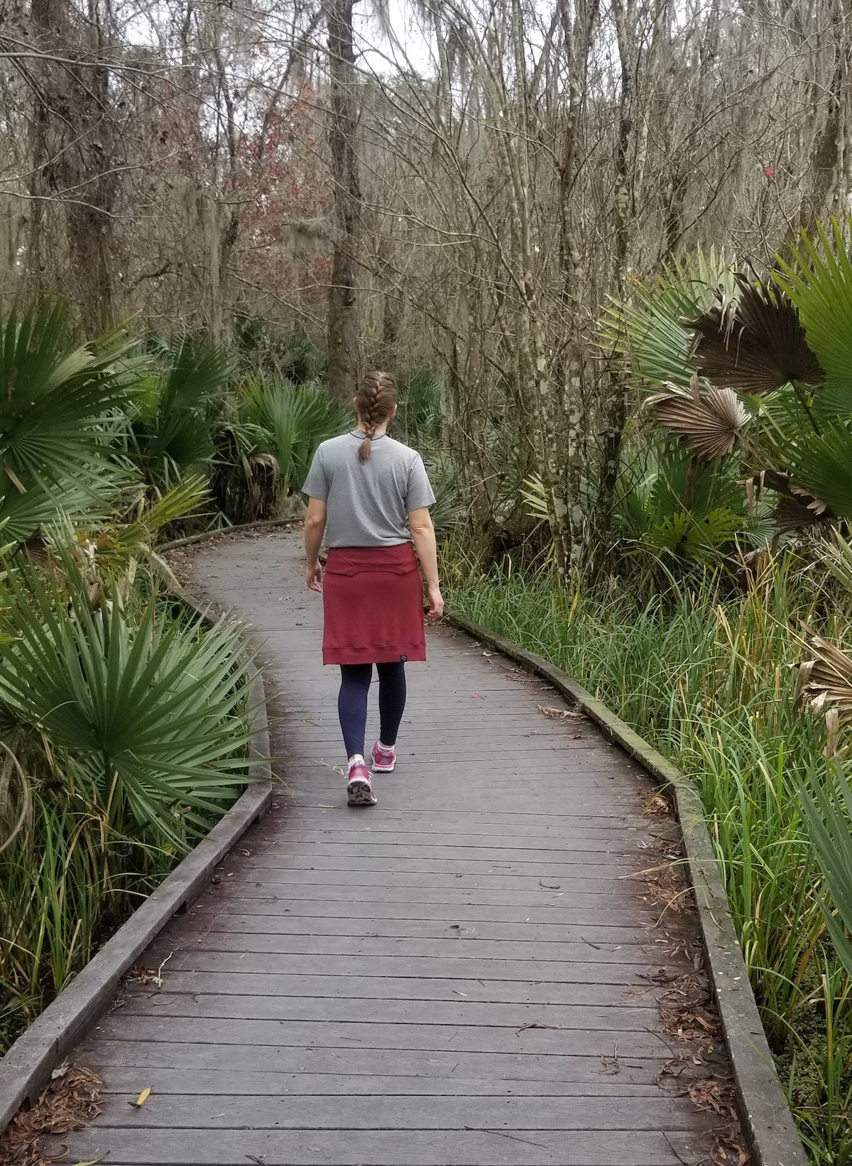 hiker walks along a boardwalk with palmettos on either side