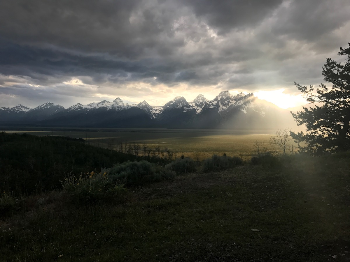 view of the snow-capped Tetons with sunlight shining through dramatic clouds