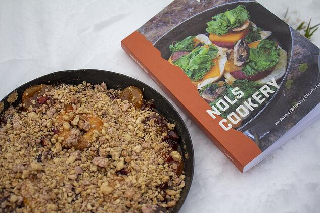 backcountry fruit pie and 7th edition of the NOLS Cookery placed in the snow