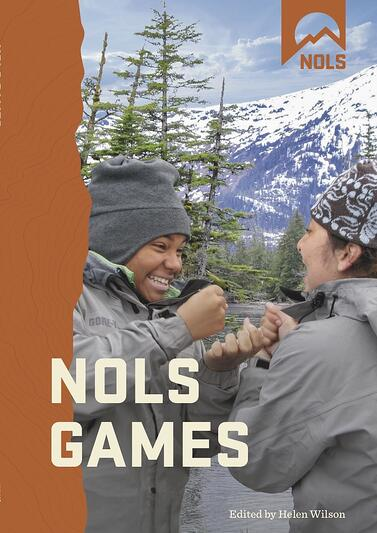 cover of NOLS games book smiling students playing game in the mountains