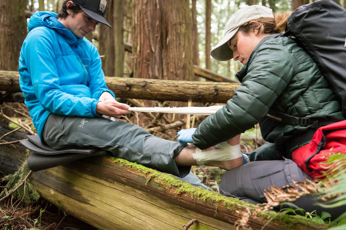 wilderness medicine student practices taping an ankle of a mock patient sitting on a log