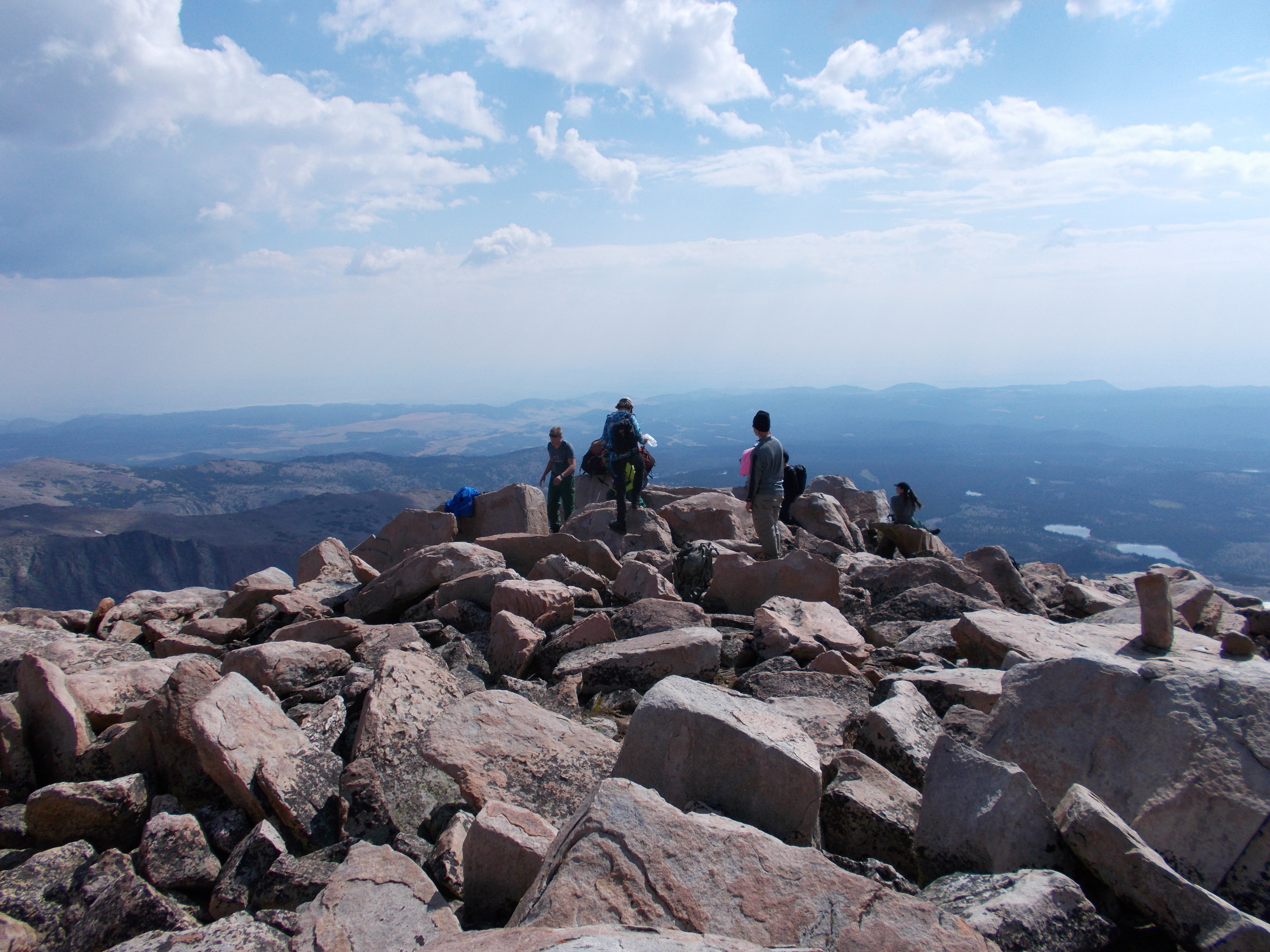 A group of four backpackers cross a boulder field with a large mountain range in front of them.
