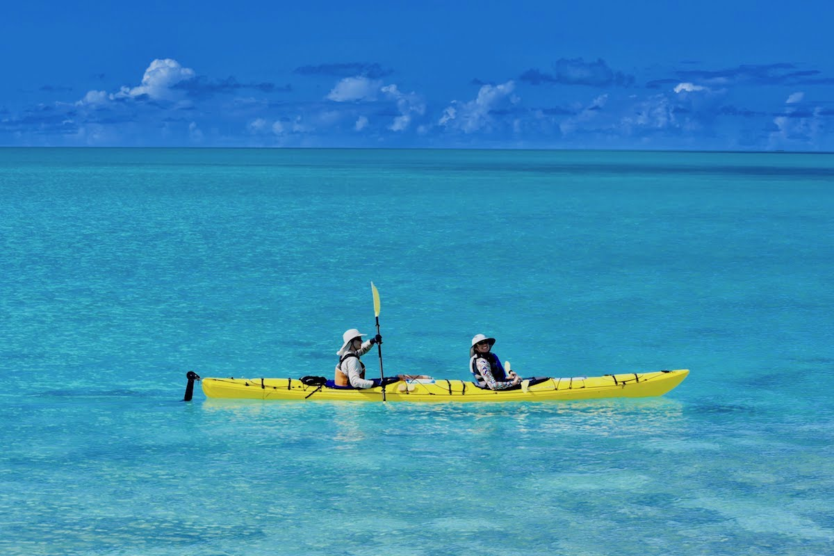 NOLS participants paddle a yellow double kayak in turquoise water in Baja