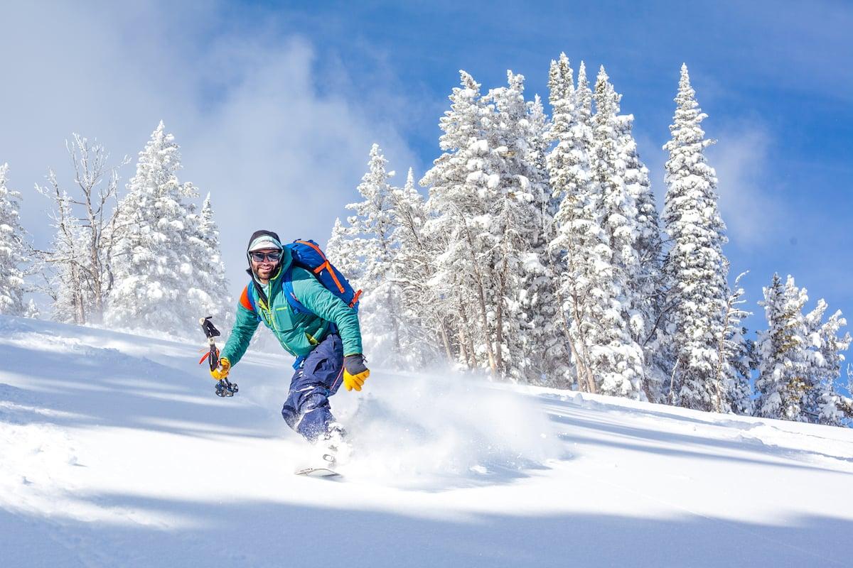 smiling NOLS participant splitboarding in fresh snow in the Rockies