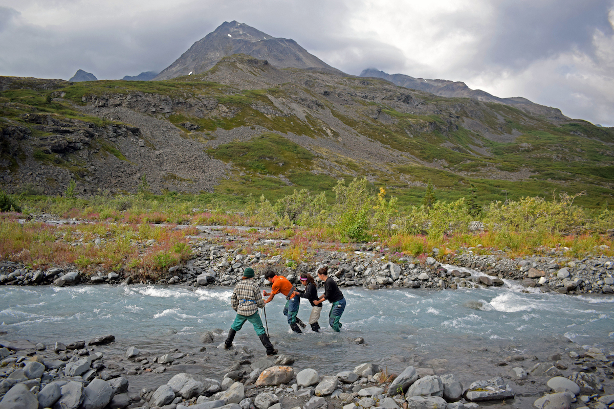 four NOLS students cross a river in Alaska's mountains