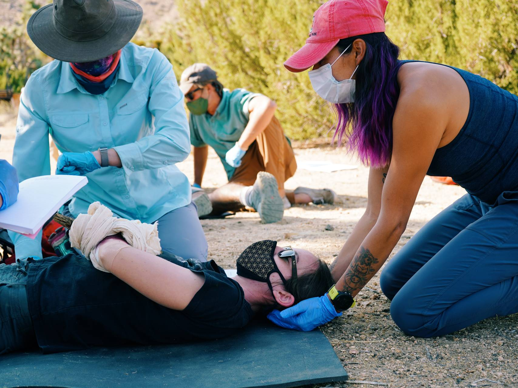 A group of three practices taking a pulse in a mock scenario