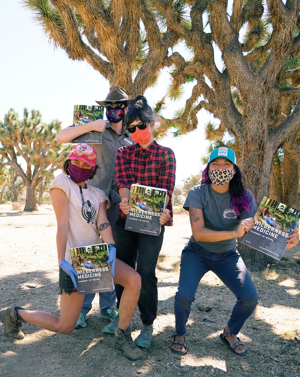 Four NOLS students smile while wearing masks and hold up the Wilderness Medicine Handbook