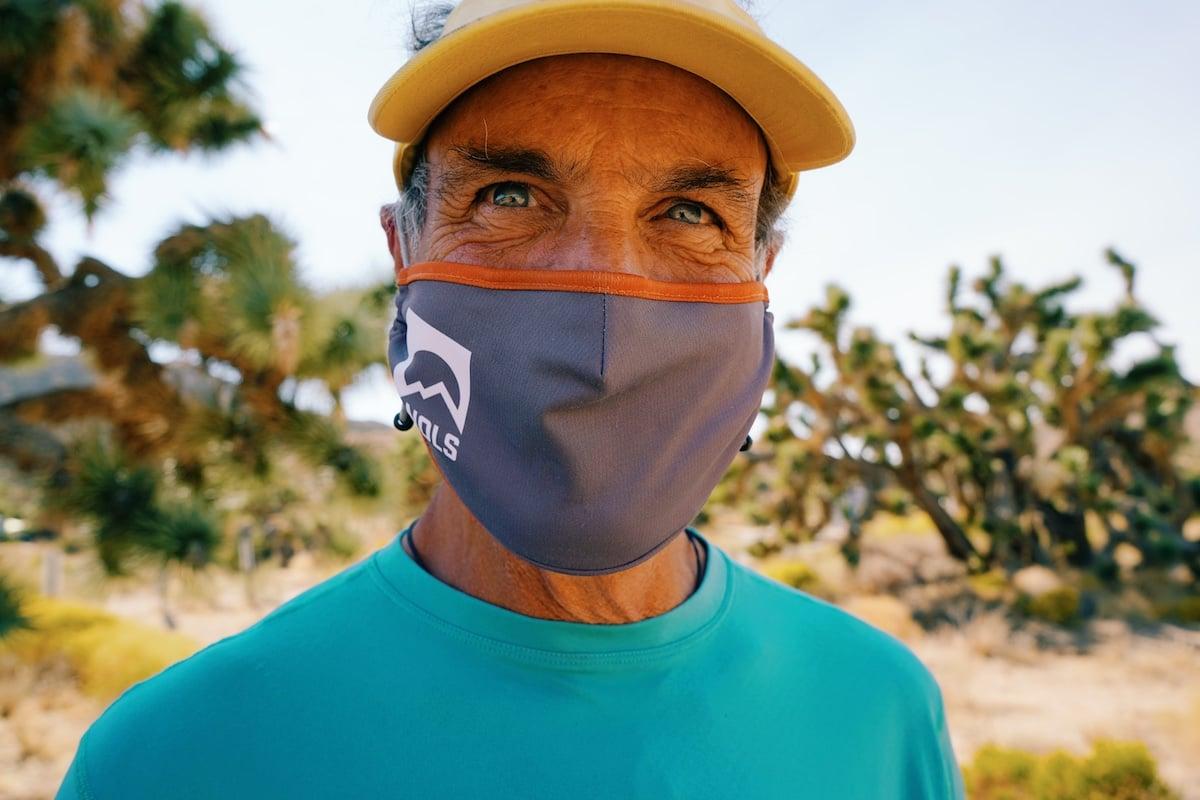 Close-up shot of a man wearing a NOLS-logo face covering