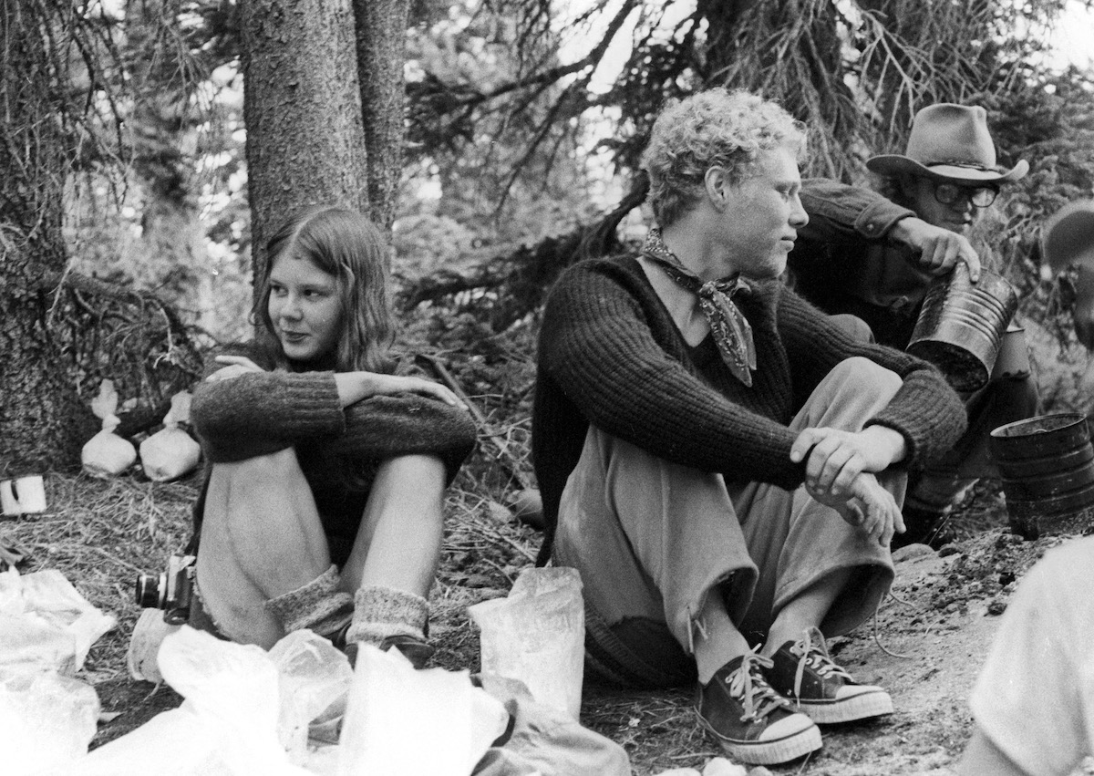 black and white photo of several NOLS students taking a break on an expedition in the 1970s with one student pouring liquid out of a billycan