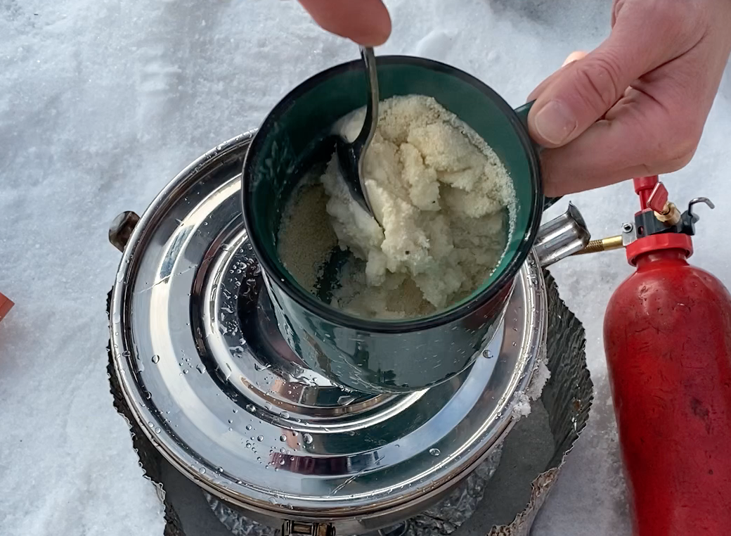 stirring potato pearls into a paste to make soup in a mug over WhisperLite stove