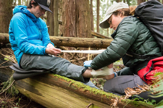 NOLS student practices taping another student's ankle in the woods