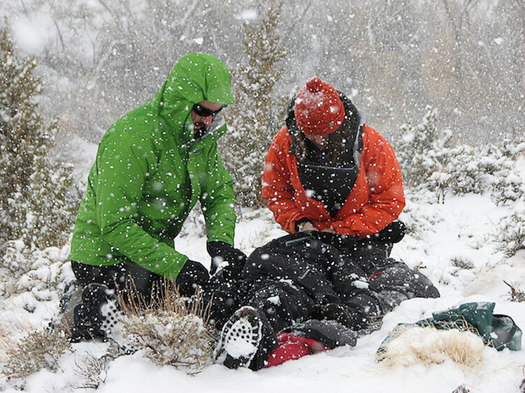 Two rescuers kneel in a snowy forrest while treating a collapsed patient.