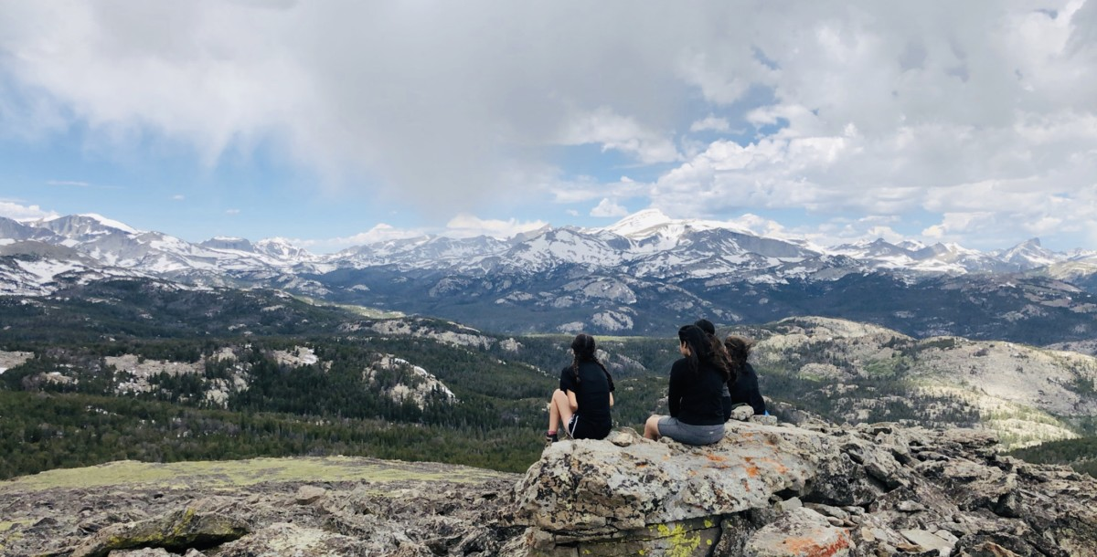 Several NOLS students overlook a mountain landscape