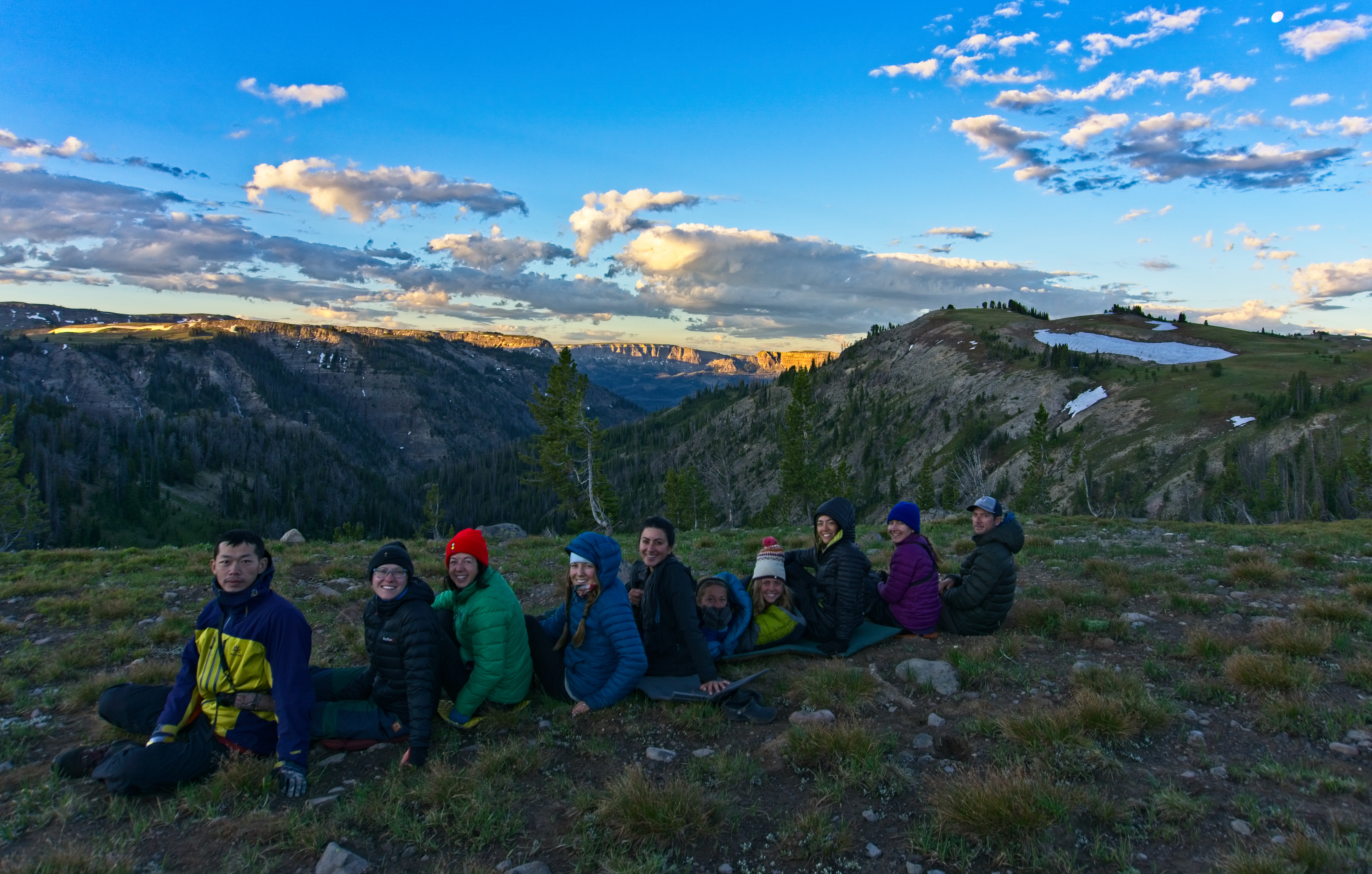 ten students sit in a line in the mountains at sunset