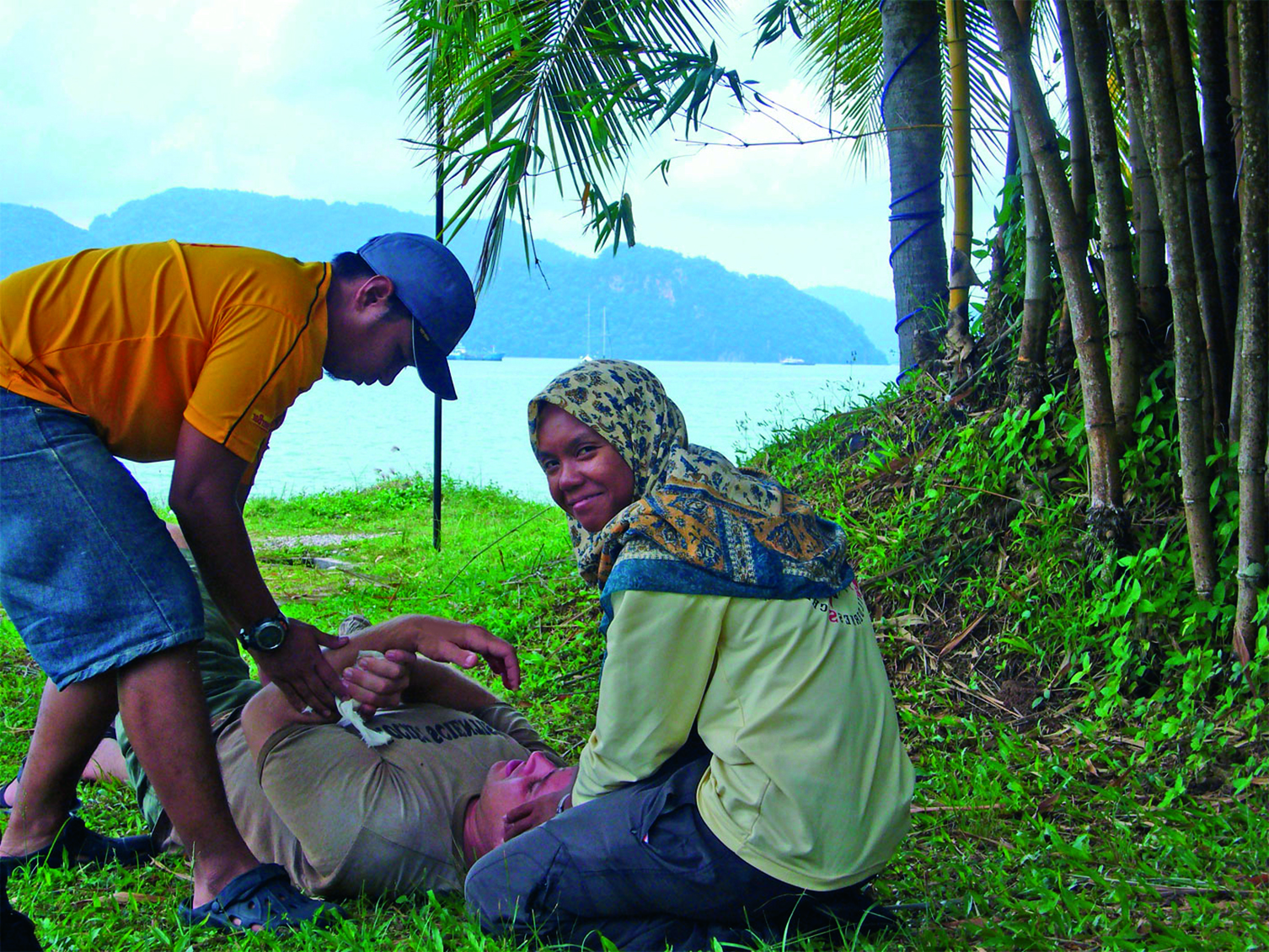 Woman wearing a head scarf and a man practice patient care on a NOLS wilderness medicine course
